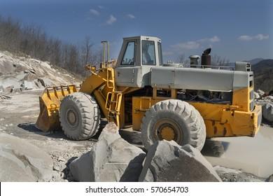 Granite quarry. Working mining machines. Mining industry.