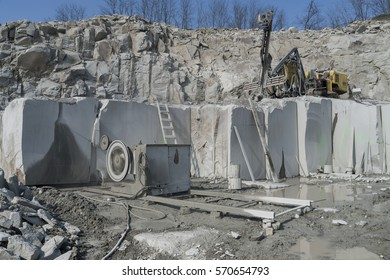 Granite quarry. Working mining machines. Mining industry.