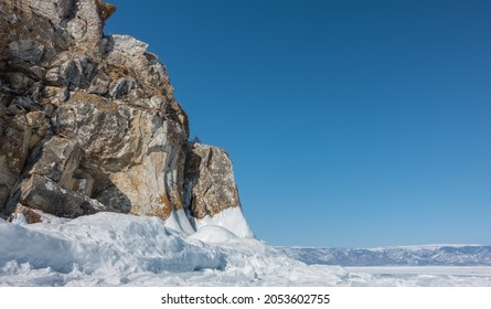 Granite rock, devoid of vegetation, against a blue sky. Steep slopes with cracks. The base is icy. Close-up. A mountain range is visible in the distance. Baikal