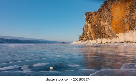 A granite rock, devoid of vegetation, rises above the frozen lake. Steep slopes, icicles at the base. Cracked ice. Reflection on the surface. Mountains in the distance against the blue sky. Baikal.