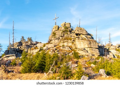 Granite rock formation with wooden cross on the top of Hochstein near Dreisesselberg, Tristolicnik. Border between Bayerische Wald in Germany and Sumava National Park in Czech Republic.