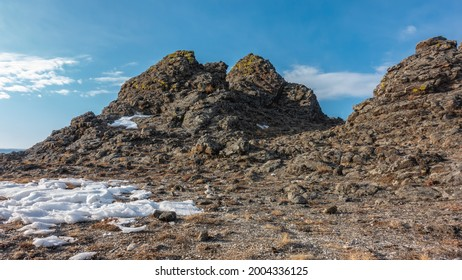 Granite rocks, devoid of vegetation, against the background of the blue sky. Cracks and yellow lichens on the rocks. Snow and dry grass on the ground. Siberia. Sunny winter day