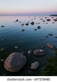 Granite rocks of Gulf of FInland in front of blue and magenta cloudy sky at sunset