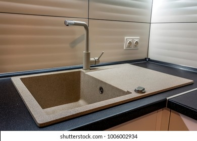 Granite sink and water faucet in new modern kitchen interior