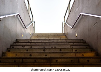Granite staircase with handrails at the entrance of an underground pedestrian tunnel.