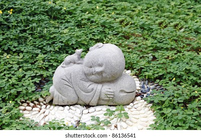 Granite statue of a cute baby monk with a rat which is the first animal zodiac sign in the Chinese horoscope, in a green park.