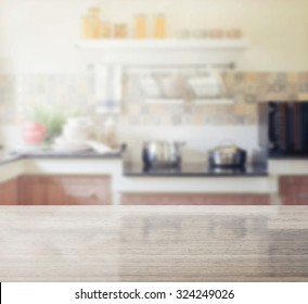 granite table top and blur of modern kitchen interior as background