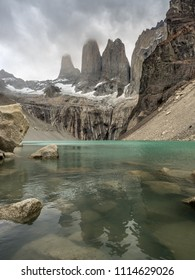 The granite Torres del Paine are reflected in the green glacial waters at the door of the lake. Submerged boulders fill the foreground and dark clouds frame the Torres.