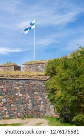 Granite walls of the historic fort Suomenlin Sveaborg in Finland on a summer day and the flag of Finland on fortifications.