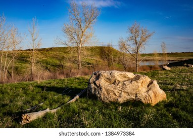 Granitic boulder on green grass with blue sky in spring time. Lake in background