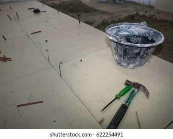 Granito tile floor under installation with bucket and hammer for house building