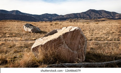 granitoidschist boulder on grassy prairie with rocky mountains in background and white altostratus clouds