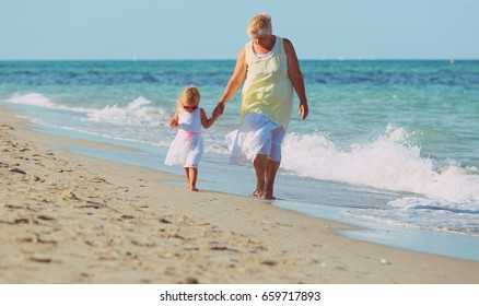 granmother with little granddaughter walk on beach