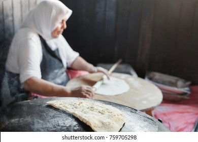 Granny chef cook Turkish pancake Gozleme on the stove