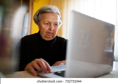 Granny communicating with her friends using a laptop.