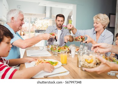 Granny giving food to granddad while sitting at dining table with family