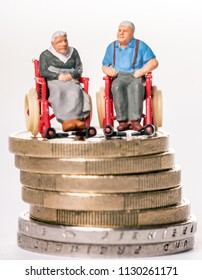 Granny and grandpa in a wheelchair on a money stack