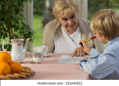Granny helping his grandson with doing homework
