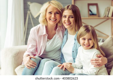 Granny, her daughter and granddaughter are looking at camera and smiling while sitting on sofa at home