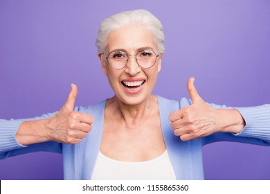 Granny recommends! Portrait of beautiful nice happy gray-haired old lady wearing casual and glasses, showing double thumbs up. Isolated over pastel violet purple background