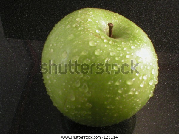 Granny Smith apple with dew on black background.