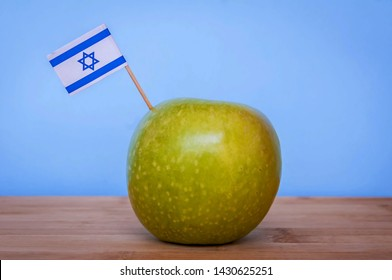 Granny Smith green apple grown in Israel with a little Israeli flag. Fruit made in Israel, Israeli fruits concept image. Jewish New Year Rosh Hashana illustration.