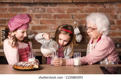 Granny with two little granddaughters sitting at table with glasses of milk and homemade pie
