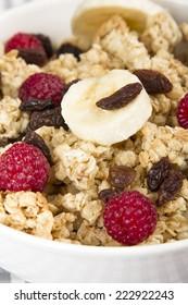 granola with banana, raspberries and raisins - nutritious breakfast
