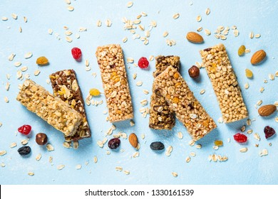 Granola bar. Healthy  snack. Cereal granola bar with nuts, fruits and berries on a blue stone table. Top view.