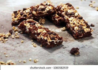 Granola bar. Healthy sweet dessert snack. Cereal granola bar with nuts, fruit, chocolate and berries on a stone table.
