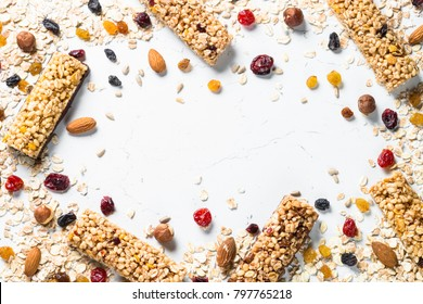 Granola bar and ingredients on a white stone table. Cereal granola bar with nuts, fruit and berries. Top view copy space.