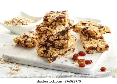 Granola bar with raisins on white wooden background
