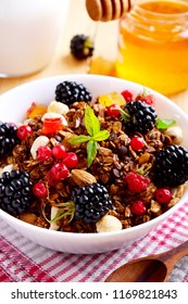 Granola with berries, honey and milk for breakfast