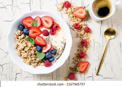 Granola with berries, yoghurt and coffee for breakfast. Cereal oats with strawberries, blueberries and raspberries for healthy eating. Top view