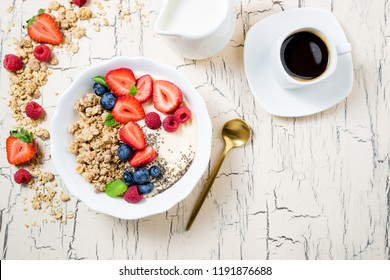Granola with berries, yoghurt and coffee for breakfast. Cereal oats with strawberries, blueberries and raspberries for healthy eating. Top view, copy space