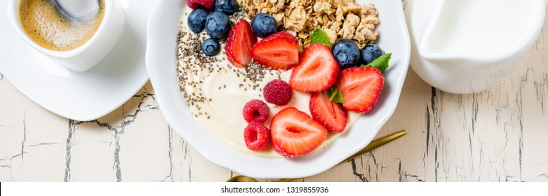 Granola with berries, yoghurt and coffee for breakfast. Cereal oats with strawberries, blueberries and raspberries for healthy eating. Long web format