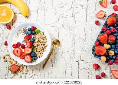 Granola with berries, yoghurt and fruits for breakfast. Cereal oatmeal with strawberries, blueberries and raspberries. Muesli with fruits and berries. Diet, healthy food concept