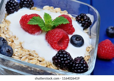Granola with berries and yoghurt in a transparent bowl on blue wooden table