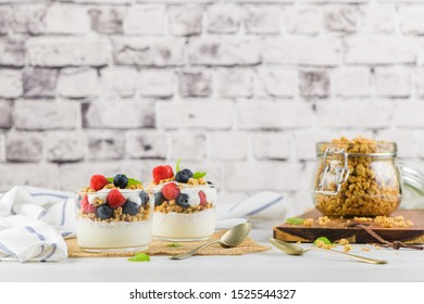 Granola blackberries and raspberries homemade yogurt in glass on light white wooden background. Healthy food concept.