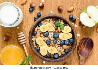Granola bowl with blueberries, banana slices, apple, honey and milk. Table top view. Concept of healthy lifestyle, healthy eating, dieting, fitness, vegan, vegetarian