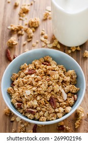 granola in bowl in brown background and bottle of milk