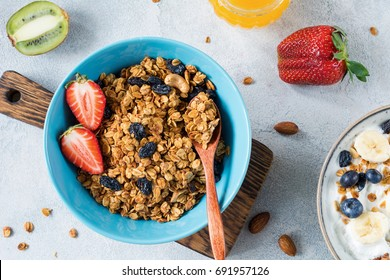 Granola bowl with dried raisins, nuts and fresh fruits. Table top view healthy breakfast food