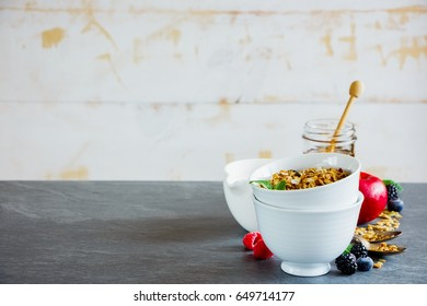 Granola in bowls. Breakfast set with granola, milk, honey and fresh organic fruits, white wooden wall background, selective focus. Clean eating, vegan, vegetarian, weight loss, healthy food concept