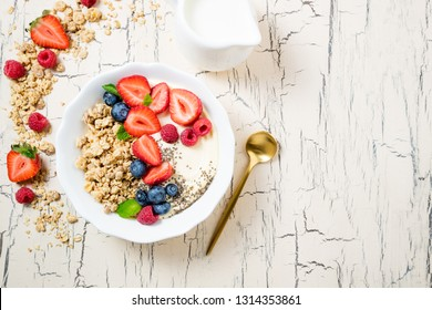 Granola for breakfast with berries and yoghurt. Cereal oatmeal or  muesli with strawberries, blueberries and raspberries. Concept dieting, healthy food and eating. Top view, copy space