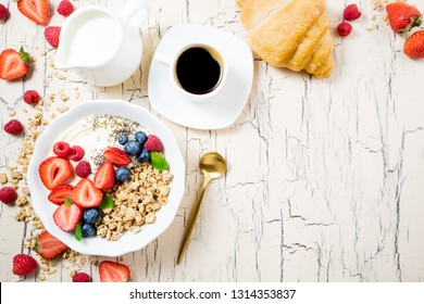 Granola for breakfast with berries, yoghurt, croissant and coffee cup. Cereal oatmeal or  muesli with strawberries, blueberries and raspberries. Concept dieting, healthy food and eating. Top view