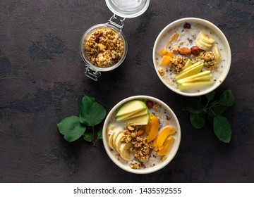 Granola breakfast with fruits, nuts, milk and peanut butter in bowl on a white background. Healthy breakfast cereal top view