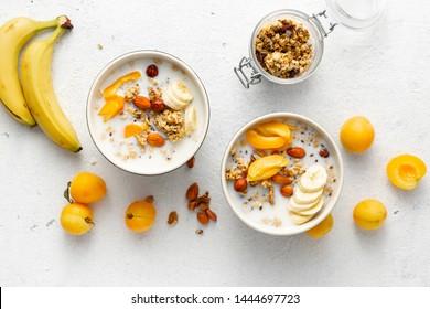 Granola Frühstück mit Früchten, Nüssen, Milch und Erdnussbutter in Schüssel auf weißem Hintergrund. Gesundes Frühstücksbuffet, Draufsicht