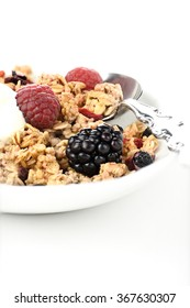 Granola breakfast muesli on a spoon with currants and fresh fruit against a white background. Concept image for healthy eating. Copy space.