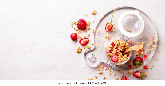 Granola Cereal bar with Strawberries on the Gray Background in a glass jar. Muesli with  fruit and berries Useful Breakfast. Healthy Food sweet dessert snack. Diet Nutrition Concept. Top View.