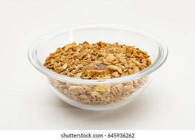 Granola cereal with dried frutis, nuts in a bowl and honey  isolated on white backgroung